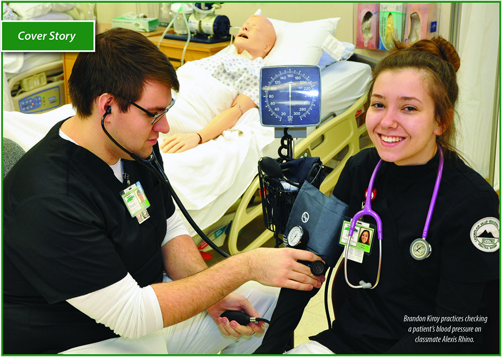 Brandon Kiroy practices checking a patient's blood pressure on classmate Alexis Rhino.